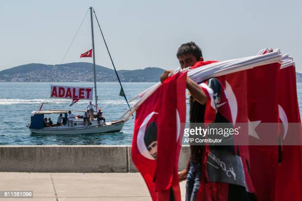 TOPSHOT A flag seller passes a boat with a banner reading 'Adalet' as Turkey's main opposition Republican People's Party leader Kemal Kilicdaroglu...