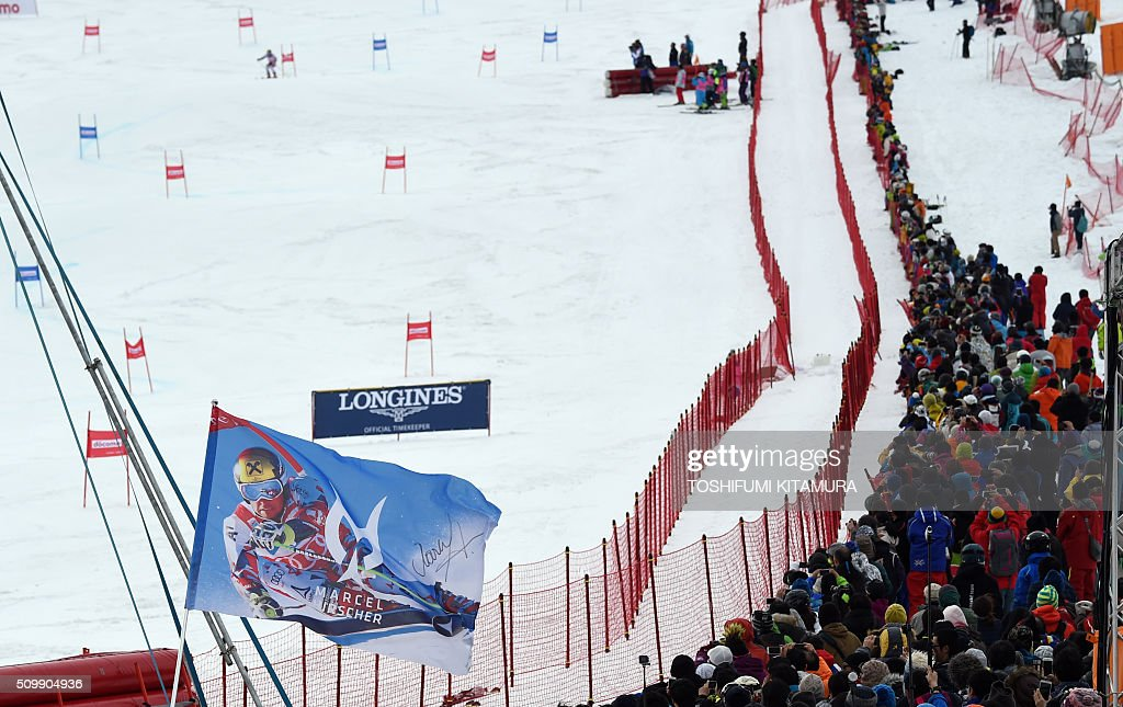 A flag showing Marcel Hirscher of Austria is seen held by a fan as Hircher (background) skis down the course during his second run at the FIS Ski World Cup 2015/2016 6th men's giant slalom in Naeba, Niigata prefecture on February 13, 2016. AFP PHOTO / TOSHIFUMI KITAMURA / AFP / TOSHIFUMI KITAMURA
