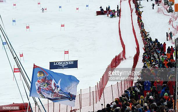 A flag showing Marcel Hirscher of Austria is seen held by a fan as Hircher skis down the course during his second run at the FIS Ski World Cup...