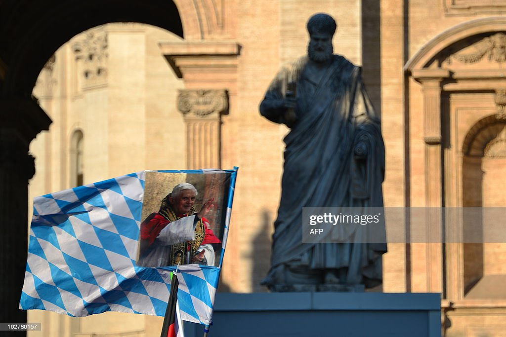 A flag showing Pope Benedict XVI is waved next to the statue of St Peter's on St Peter's square ahead of Pope Benedict XVI last weekly audience on February 27, 2013 at the Vatican. Pope Benedict XVI will hold the last audience of his pontificate in St Peter's Square on Wednesday on the eve of his historic resignation as leader of the world's 1.2 billion Catholics. AFP PHOTO / GABRIEL BOUYS