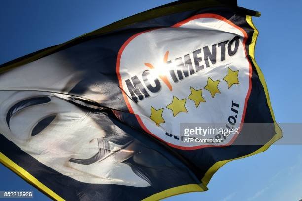 A flag showing the logo of Italy's populist Five Star Movement and a Guy Fawkes mask is pictured ahead of the party's congress in Rimini on September...