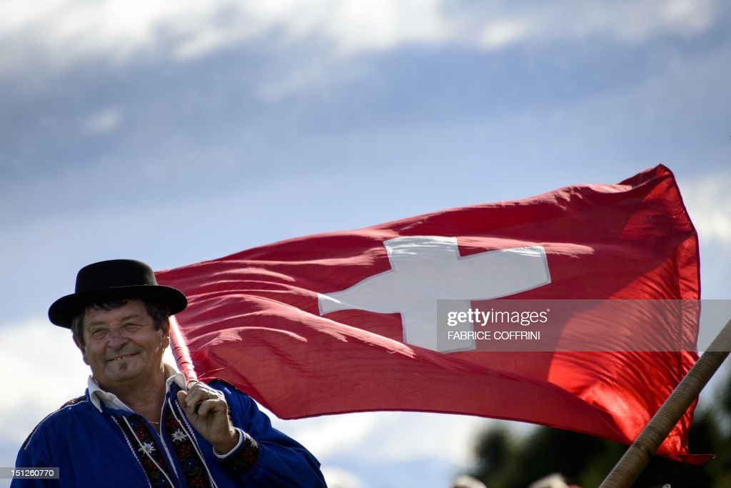 A flag thrower holds a Swiss flag during the trophy ceremony of the European Masters golf tournament at Crans-Sur-Sierre Golf Club on September 2, 2012 in Crans Montana.