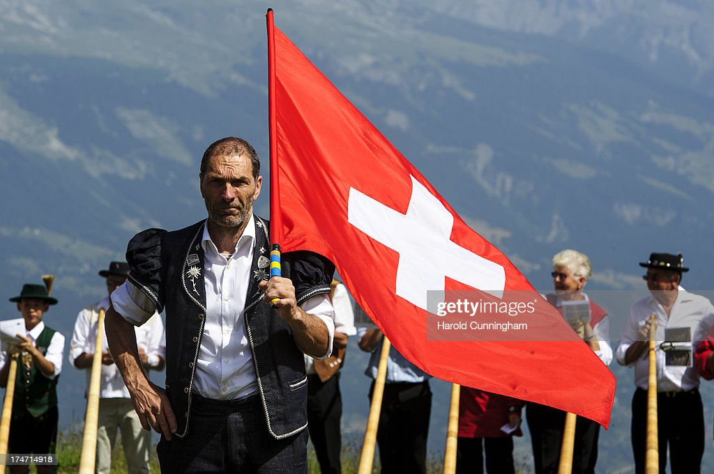A flag thrower looks on as alphorn players prepare to perform on July 28, 2013 in Nendaz, Switzerland. About 150 alphorn blowers performed together on the last day of the international Alphorn Festival of Nendaz. The Swiss folkloric wooden wind instrument was used in most mountainous regions of Europe by mountain dwellers as signal instruments.