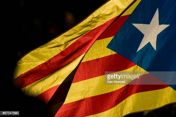 A flag waves as thousands of citizens gather in Plaza Universitat during a regional general strike to protest against the violence that marred...