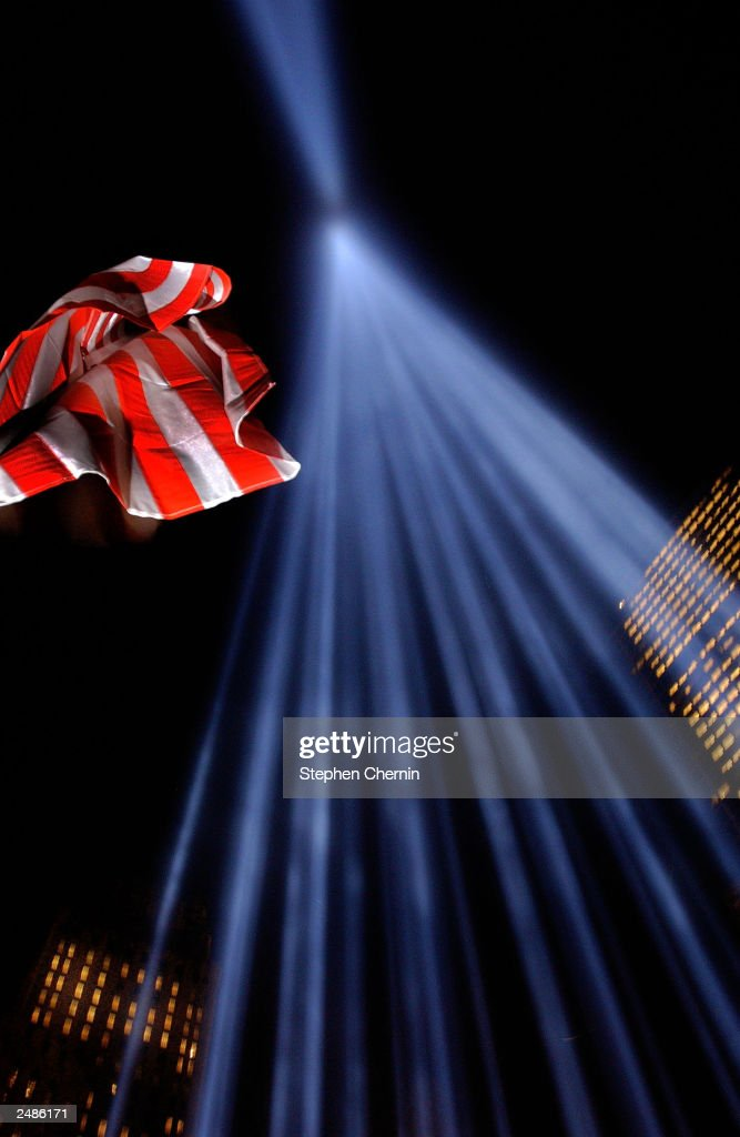 S. flag waves next to the memorial of two columns of light, known as the 'Tribute in Light,' at Ground Zero September 11, 2003 in New York City. Today marks the two-year anniversary of the September 11, 2001 terrorist attacks on the U.S.