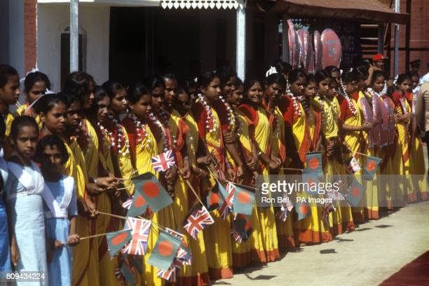 Flag waving children line up waiting to welcome the Queen on her visit to Bangladesh