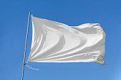 White flag attached to a flagpole waving on the sky