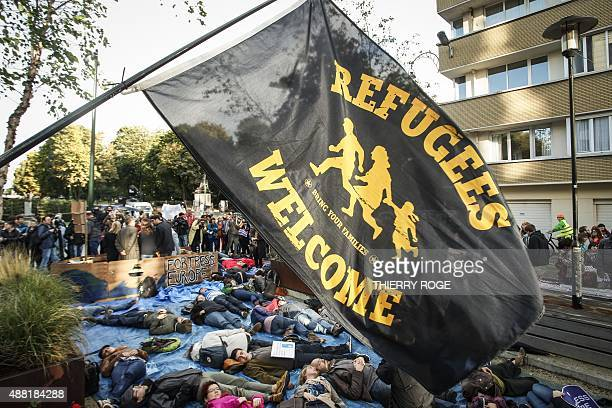 A flag welcoming refugees flies over protesters lying on the ground during a protest outside the EU headquarters in Brussels to demand shelter and...