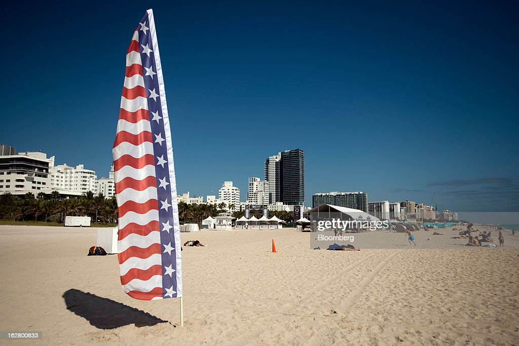 A U.S. flag wind banner stands in the sand in the South Beach neighborhood of Miami Beach, Florida, U.S., on Wednesday, Feb. 20, 2013. U.S. exports in the travel and tourism sector reached $168.1 billion in 2012, up 10.1 percent from the year-ago level of $152.7 billion, according to data released Feb. 22 by the Commerce Department's International Trade Administration. Photographer: Ty Wright/Bloomberg via Getty Images