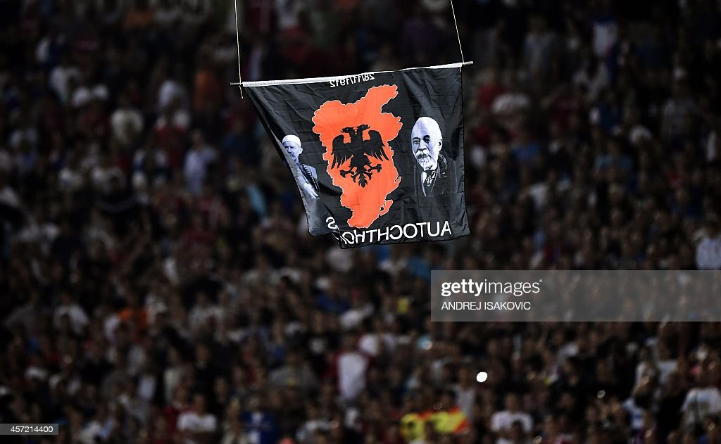 A flag with Albanian national symbols attached to a remotely operated drone flies in the stadium during the EURO 2016 group I football match between...