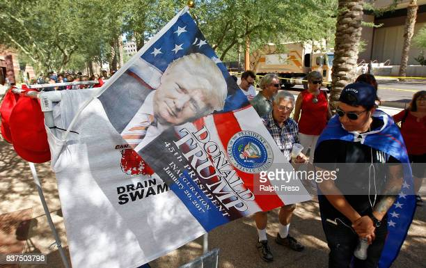 A flag with the image of US President Donald Trump hangs off a vendor's cart as a line of supporters wait to enter the Phoenix Convention Center for...