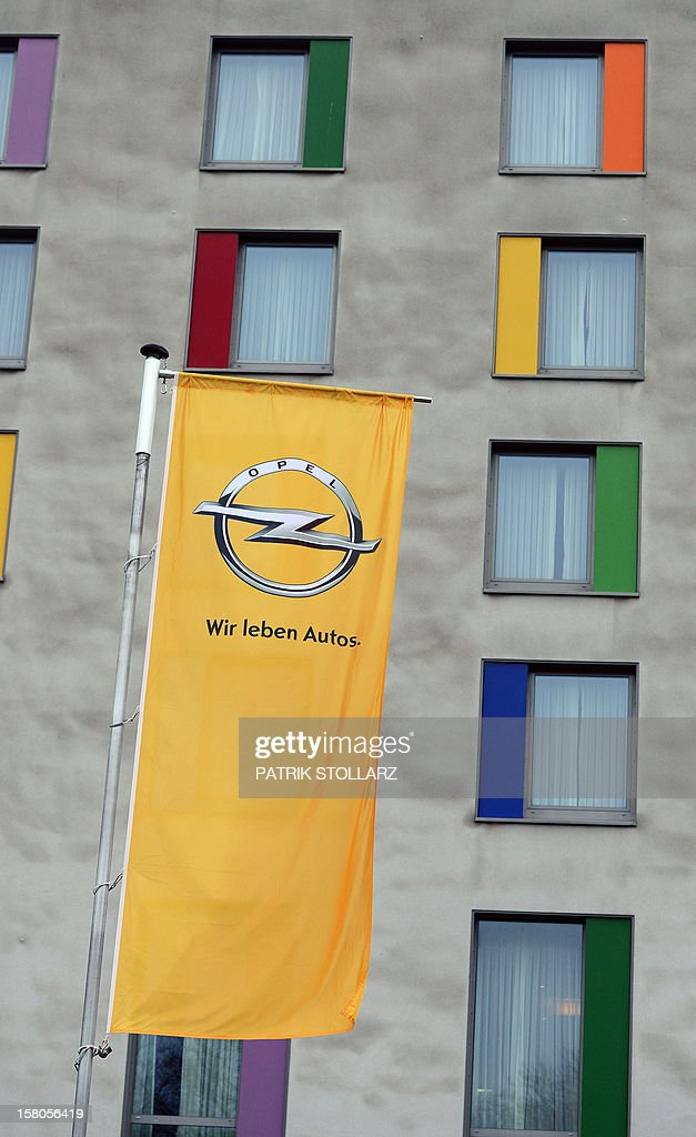 A flag with the logo of car maker Opel is seen in front of the Bochum Congress Center in Bochum, western Germany, on December 10, 2012. Opel, the loss-making German arm of US auto giant General Motors, said it would halt auto production at its Bochum plant in 2016 but pledged to keep it running as a parts distribution centre. AFP PHOTO / PATRIK STOLLARZ