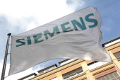 A flag with the logo of the German industrial giant Siemens AG flys at the historic construction plant on October 12 2011 in Berlin AFP PHOTO /...