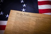 A United States flag with thirteen stars and the Constitution laying on it