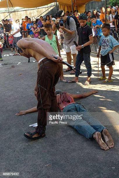 A flagellant lying on the pavement facedown gets a whip from an his executioner