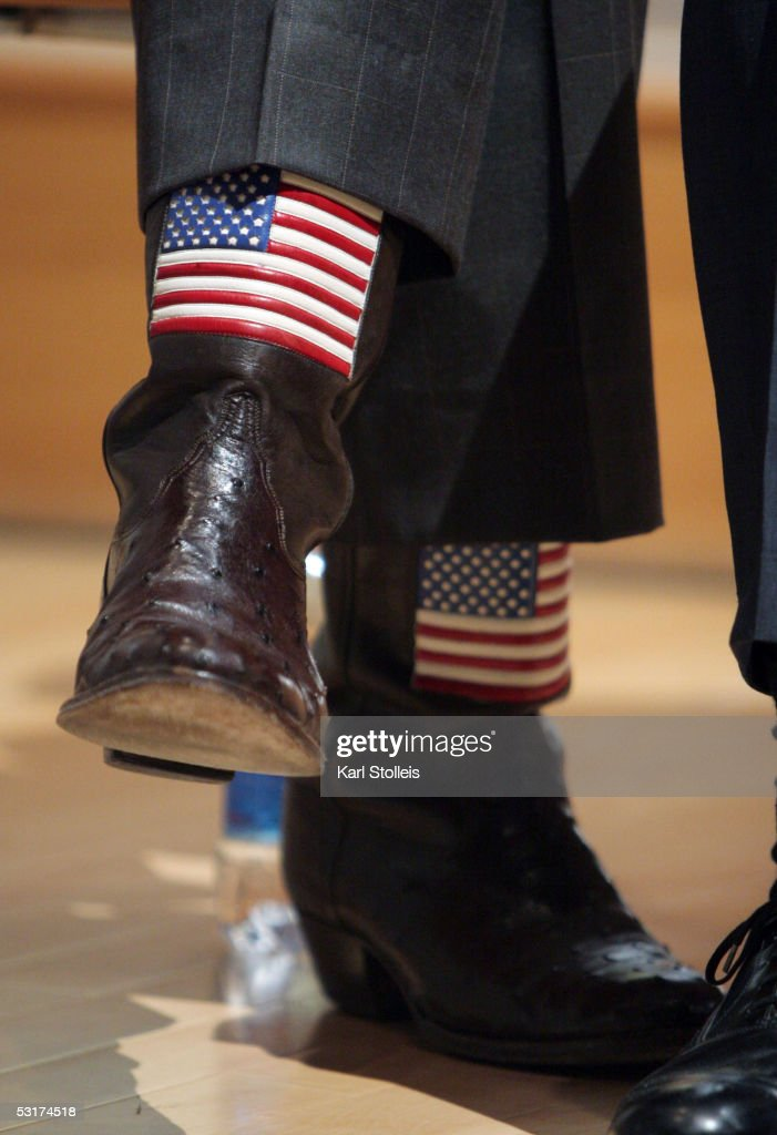 S flags adorn the boots of Texas Governor Rick Perry as he awaits his turn to speak during a news conference annoucing the opening of the Ericsson US...