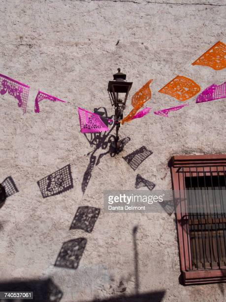 Flags against grey wall, San Miguel de Allende, Mexico