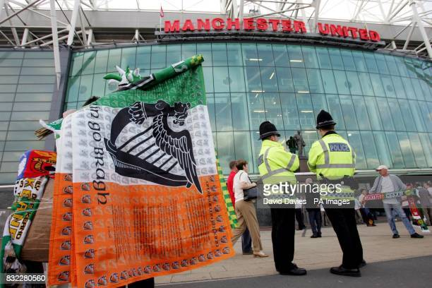 Flags and scarves are sold outside the ground ahead of the UEFA Champions League Group F match between Manchester United and Celtic at Old Trafford...