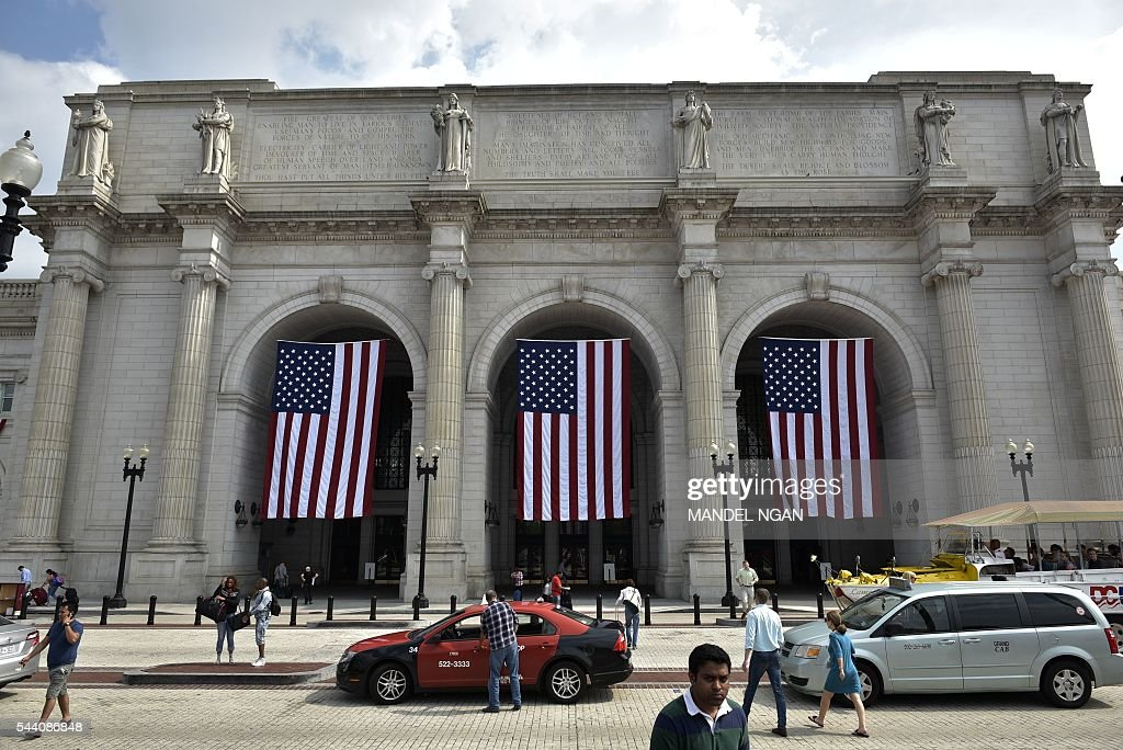 US flags are seen outside of Union Station on July 1, 2016, ahead of the Independence Day holiday weekend, in Washington, DC. / AFP / Mandel Ngan