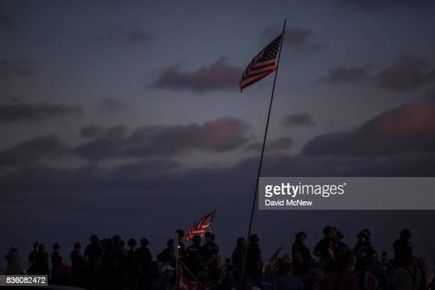 Flags are waved as police form a line to keep demonstrators and counter demonstrators apart at an 'America First' demonstration on August 20 2017 in...
