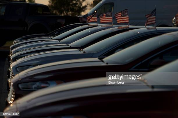 US flags fly above a row of Ford Motor Co 2014 Fusion vehicles at Rod Baker Ford dealership in Plainfield Illinois US on Wednesday July 23 2014 Ford...