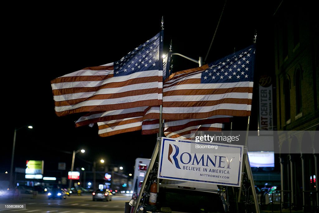 Flags fly above a sign for Republican presidential candidate Mitt Romney on a truck prior to a Romney campaign rally at the Verizon Wireless Center in Manchester, New Hampshire, U.S., on Monday, Nov. 5, 2012. President Barack Obama beseeched core supporters and wayward backers to go to the polls, while Romney reached for an upset victory powered by anti-incumbent fervor on the final full day of a race that polls suggest has tilted slightly in the president's favor. Photographer: Andrew Harrer/Bloomberg via Getty Images
