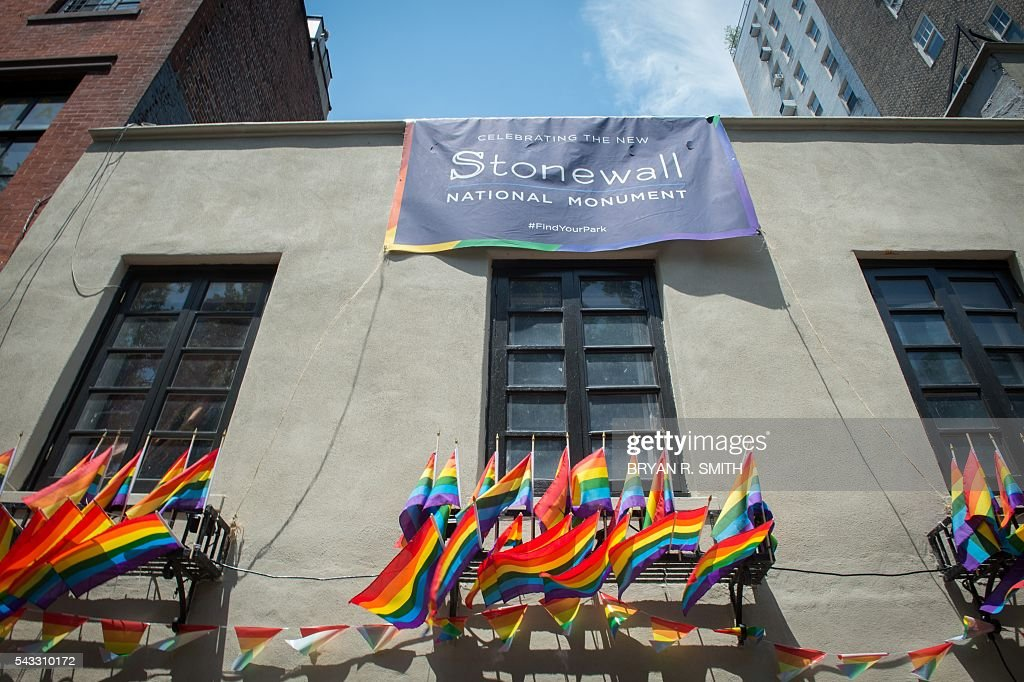 Flags fly form the Stonewall Inn as Mayor Bill de Blasio joins elected officials, advocates and New Yorkers in designating Stonewall Inn a National Monument, on June 27, 2016 in New York. / AFP / Bryan R. Smith