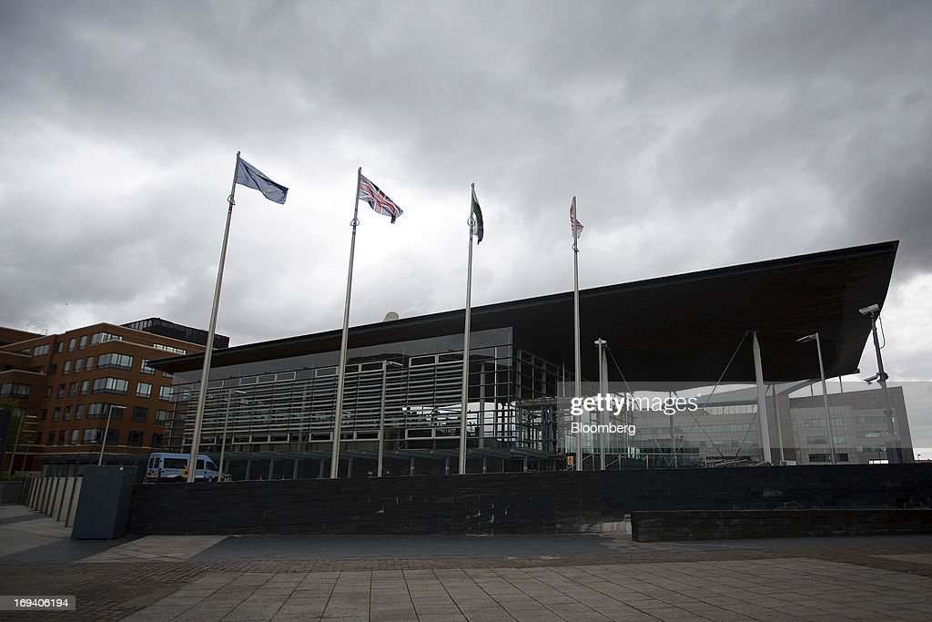 Flags fly from flagpoles outside the Senedd, or National Assembly for Wales, government building in Cardiff, U.K. on Thursday, May 23, 2013. Bank of England Markets Director Paul Fisher said policy makers must continue to provide support to the British economy so that companies and consumers have room to reduce debts and rebuild confidence. Photographer: Simon Dawson/Bloomberg via Getty Images
