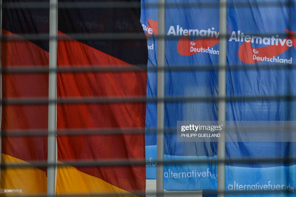 Flags fly in front of the venue of the german right wing party Alternative for Germany (AfD) at the the Stuttgart Congress Centre ICS on April 30, 2016. The Alternative for Germany (AfD) party is meeting in the western city of Stuttgart, where it is expected to adopt an anti-Islamic manifesto, emboldened by the rise of European anti-migrant groups like Austria's Freedom Party. / AFP / Philipp GUELLAND