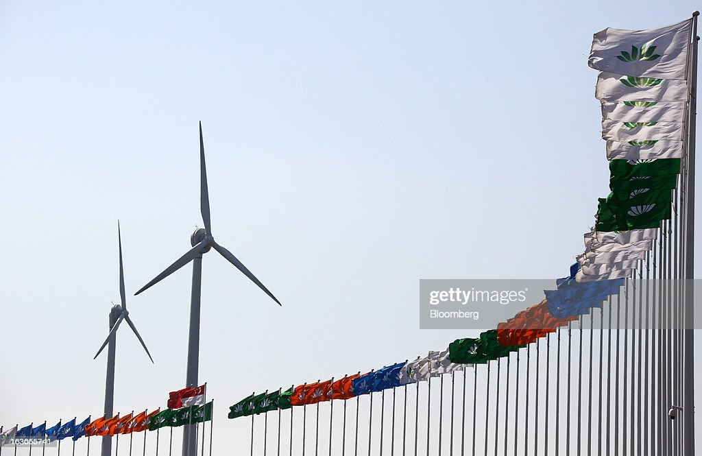 Flags fly in front of wind turbines at the Sino-Singapore Tianjin Eco-city in Tianjin, China, on Wednesday, March 13, 2013. China's money-market rate rose to a one-week high after central bank Governor Zhou Xiaochuan said yesterday the nation should be on 'high alert' over inflation. Photographer: Tomohiro Ohsumi/Bloomberg via Getty Images