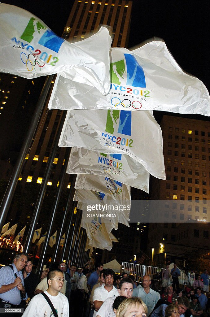 NYC2012 flags fly in the wind as people watch the New York City Olympic bid committee present their proposal to host the 2012 Olympics at a meeting...