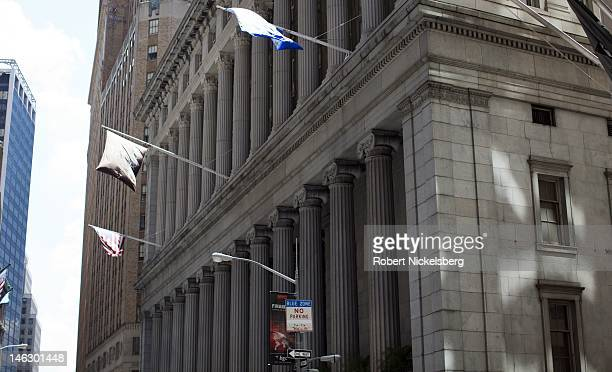 Flags fly on a building at 55 Wall Street near Federal Hall June 7 2012 and the New York Stock Exchange in New York City