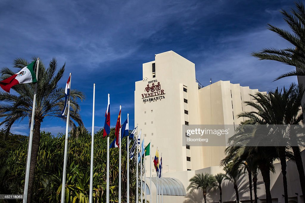 Flags fly outside the state-run Venetur Hotel, the site of the first Russia-Venezuela Oil Congress, on Margarita Island in Nueva Esparta, Venezuela, on Thursday, Nov. 21, 2013. OAO Rosneft, Russia's largest oil producer, plans to invest $13 billion in five projects in Venezuela over five years and buy at least part of OAO Lukoil's stake in a producing field in the South American nation. Photographer: Meridith Kohut/Bloomberg via Getty Images