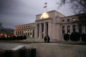Flags fly over the Federal Reserve Building on December 16 2008 in Washington DC The Fed began its last meeting of 2008 today where it is expected to...