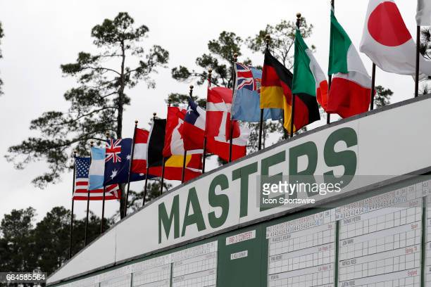 Flags from various countries wave above the scoreboard during the first day of practice for the 2017 Masters Tournament on April 3 at Augusta...