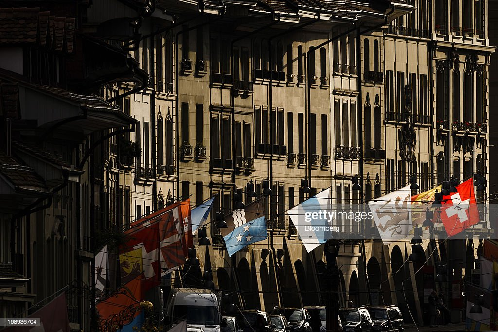 Flags, including the national flag of Switzerland, fly from a flagpole outside a row of residential homes in the old town of Bern, Switzerland, on Monday, May 13, 2013. Risks to Switzerland's housing market increased further in the first three months of the year, raising the question as to whether authorities have taken sufficient steps to prevent the bursting of a bubble. Photographer: Valentin Flauraud/Bloomberg via Getty Images