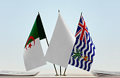 Two table flags of Algeria and BIOT with white flag between