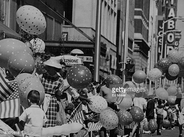 MAY 30 1962 Flags of his country and giant balloons were waved and sent into the air at the Denver parade for the astronaut adding to general...