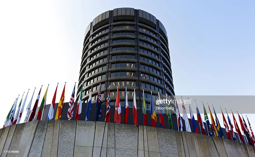 Flags of international countries hang from poles outside the headquarters of the Bank for International Settlements (BIS) in Basel, Switzerland, on Tuesday, June 25, 2013. Central banks can't expand loose monetary policy without exacerbating risks to world economies, the Bank for International Settlements said this week. Photographer: Gianluca Colla/Bloomberg via Getty Images