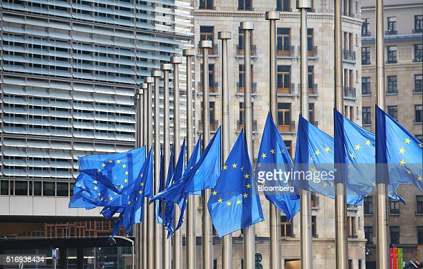 Flags of the European Union fly at halfmast outside the European Council building in Brussels Belgium on Tuesday March 22 2016 Explosions ripped...