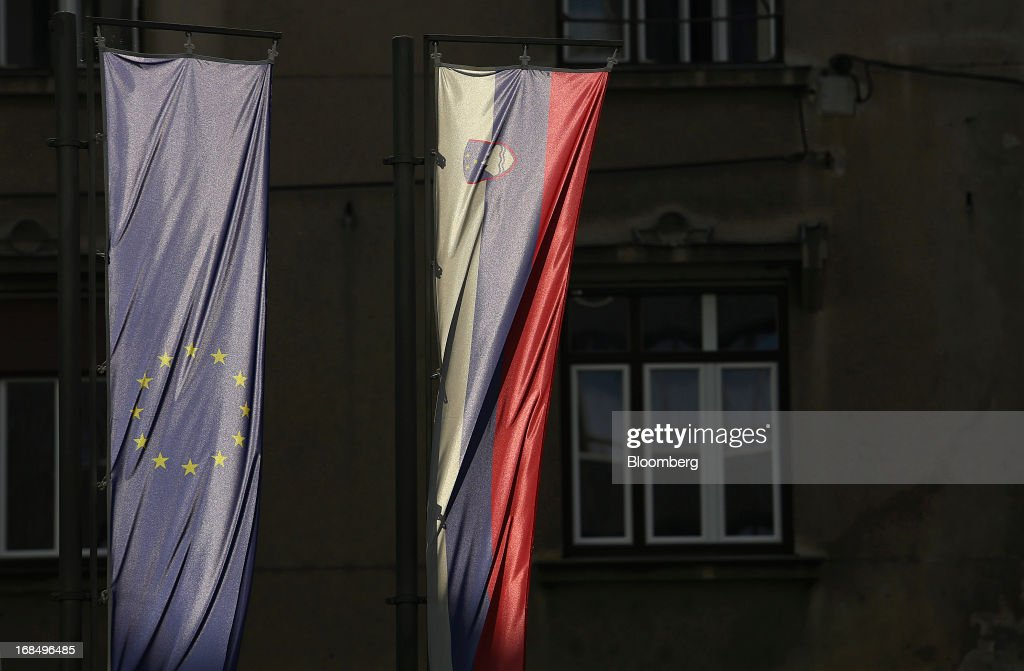 Flags of the European Union, left, and the Slovenian national flag hang from a building in Ljubljana, Slovenia, on Friday, May 10, 2013. The Adriatic nation is seeking to fix its ailing lenders with a cash injection of at least 900 million euros ($1.17 billion) after Cyprus's bailout focused investors on countries with weak banking industries. Photographer: Chris Ratcliffe/Bloomberg via Getty Images