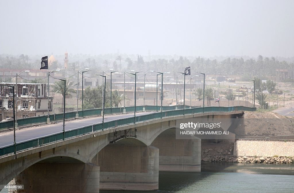 Flags of the Islamic State (IS) group flutter on Fallujah's new bridge across the Euphrates River on June 28, 2016, a few days after Iraqi forces retook the city from the jihadists. Iraqi forces took the Islamic State group's last positions in Fallujah on June 26, 2016, establishing full control over one of the jihadists' most emblematic bastions after a month-long operation. / AFP / HAIDAR