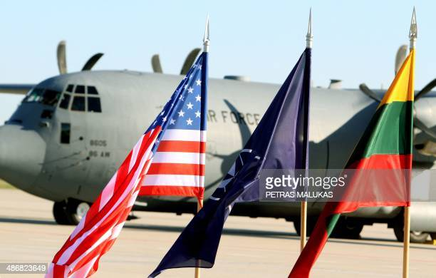 Flags of the US NATO are hoisted in front of an aircraft of the US air force carrying US soldiers at the air force base near Siauliai Zuokniai...