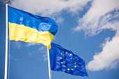 Flags of Ukraine and European Union (EU) with blue sky background