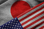3D rendering of the flags of USA and Japan on woven fabric texture. Detailed textile pattern and grunge theme.