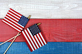High angle shot of two crossed American flags on a red, white and blue picnic table. Horizontal format with copy space.