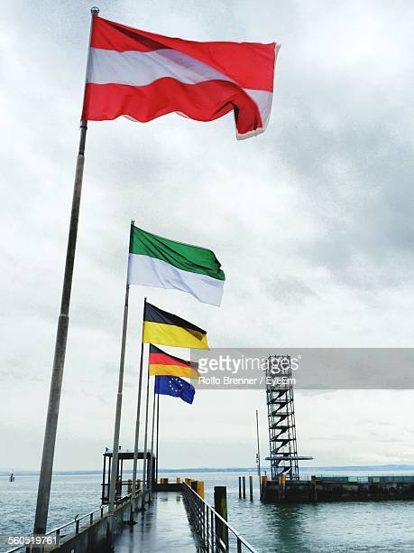 Flags On Pier Amidst Sea Against Sky