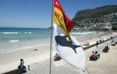 Flags warn swimmers at Fish Hoek Beach which is closed in the wake of a Great White shark attack January 13 2010 in Cape Town South Africa Witnesses...
