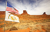 american and navajo flags waving in monument valley
