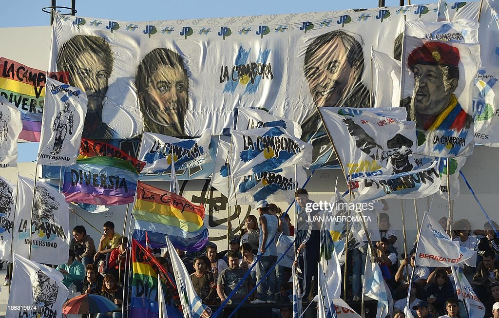 Flags with portraits (L-R) of Juan Manuel de Rosas, Jose de San Martin, Nestor Kirchner and Hugo Chavez are seen before Venezuelan President Nicolas Maduro delivered a speech at the All Boys' stadium during a political rally after a working meeting with Argentine President Cristina Fernandez de Kirchner n Buenos Aires on May 8, 2013. AFP PHOTO / Juan Mabromata